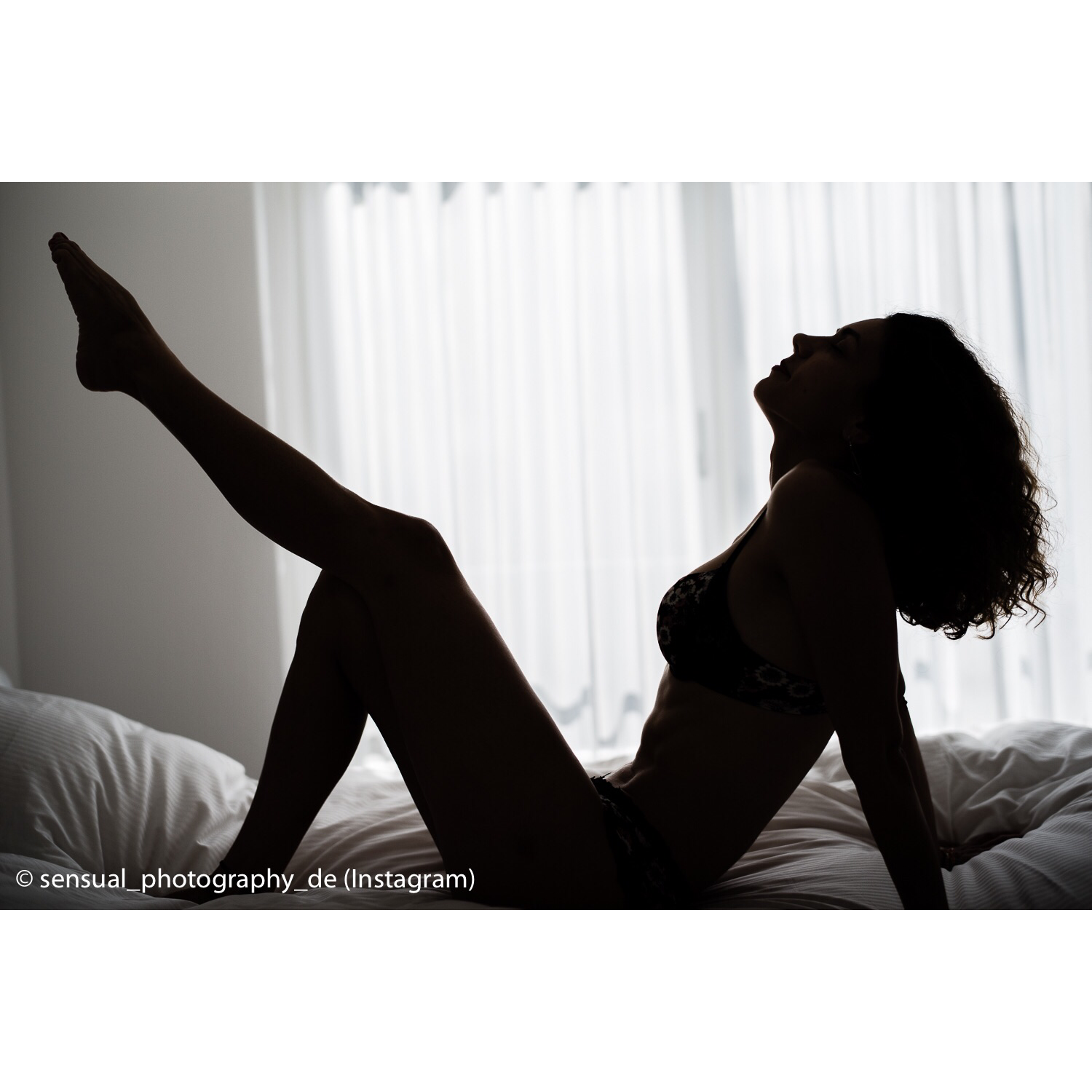 a woman's silhouette on a bed in a boat pose variation