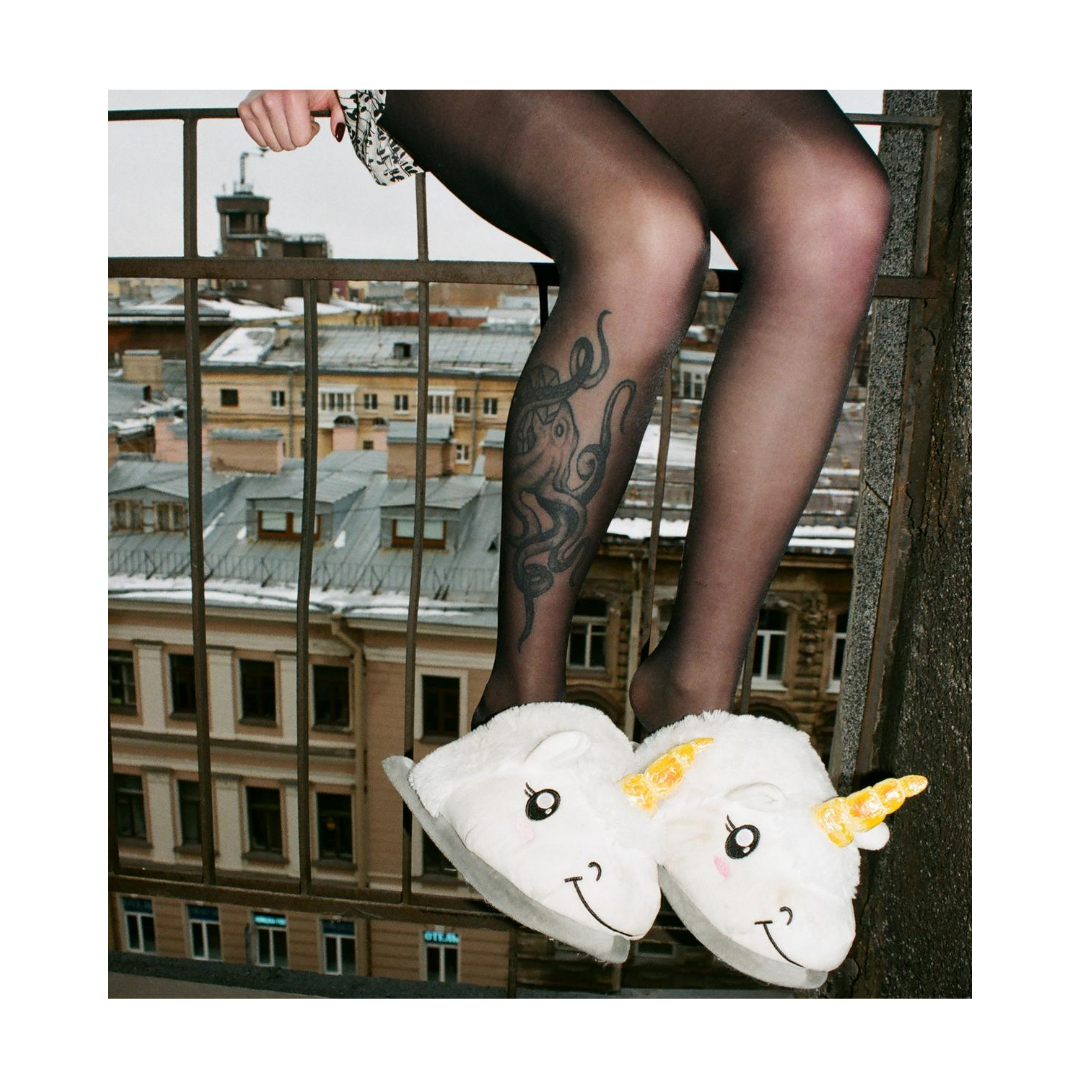 Woman sitting on a railing with unicorn slippers on